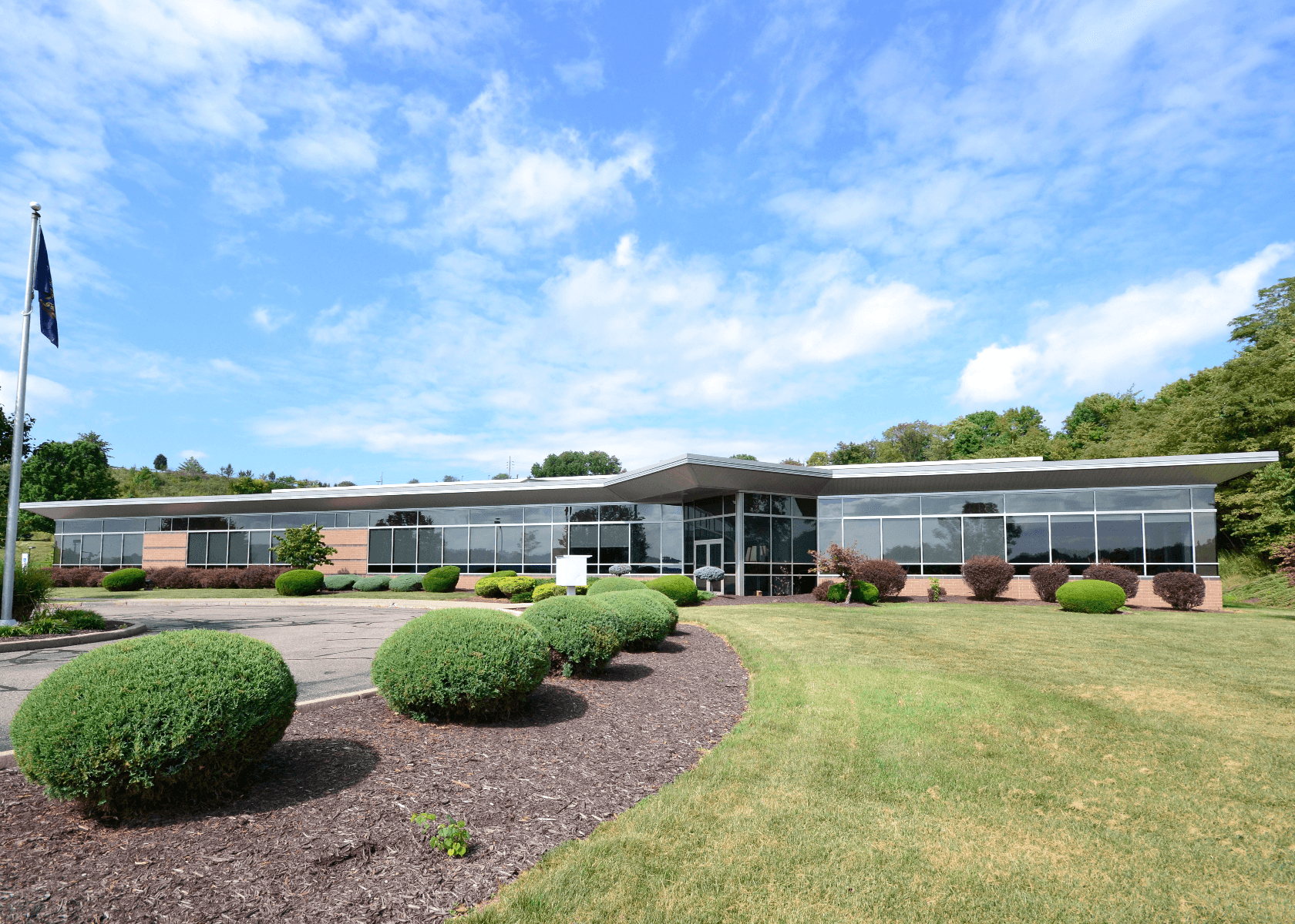 Exterior of 130 Technology Drive: A one-story office building with floor-to-ceiling windows